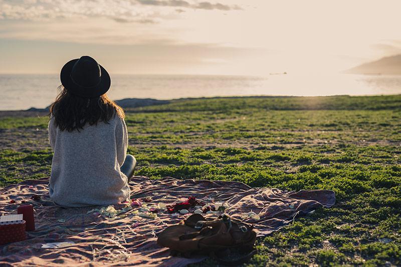 Chica observando sola la puesta de sol
