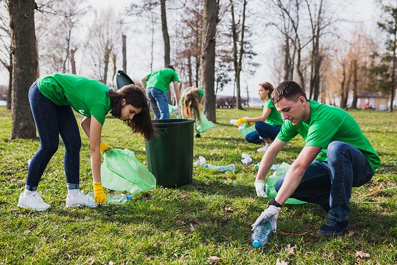 Grupo de gente realizando tareas voluntarias, recogiendo basura del suelo