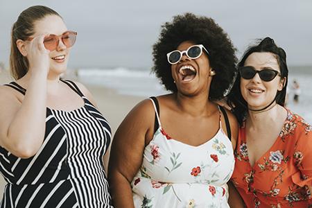 Bellas mujeres de talla grande riéndose en la playa