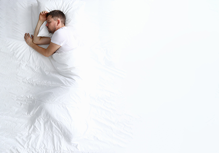 Hombre descansando correctamente en una cama con la finalidad de tener una correcta nutrición fitness
