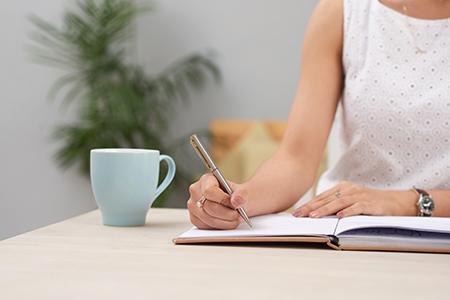 Mujer escribiendo sus sentimientos en una libreta