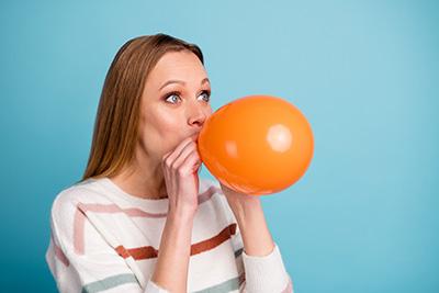 mujer inflando un globo para combatir el estrés