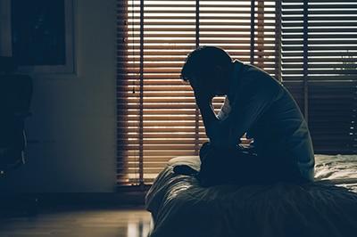 Hombre estresado encima de la cama. Reducir el estrés es uno de los beneficios de la meditación