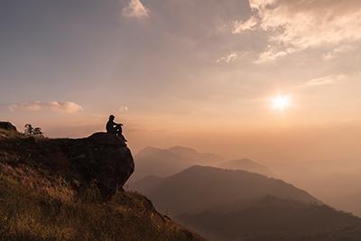 hombre reflexionando en la cima de una montaña