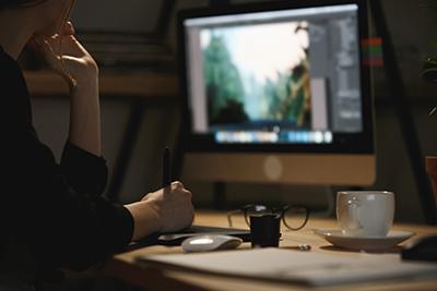Mujer concentrada enfrente del ordenador con el photoshop